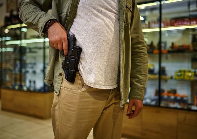 男は銃の店のホルスターからピストルを引っ張る。武器屋のインテリア、弾薬と弾薬の品揃え、銃の選択、射撃の趣味とライフスタイル、護身術