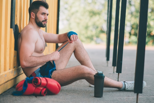Man pulls boxing bandages sits on the asphalt. gay in sportswear is preparing for sparring. boxing ring under the open sky. outdoors fighting.
