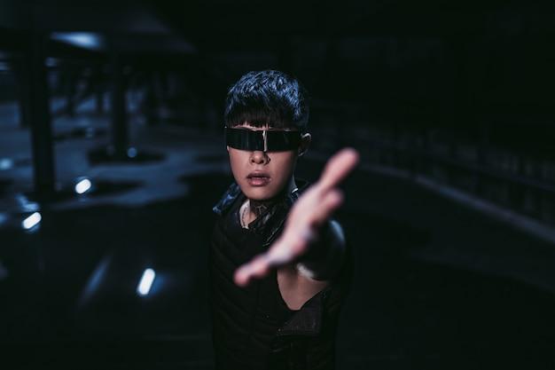 Мужчина тянет руку в темноте. концепция ближайшего будущего. киберпанк.