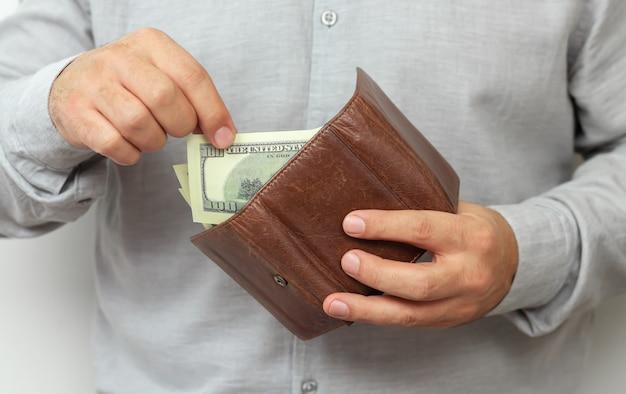 男は革の財布からお金を引き出します。金融、投資、お金の節約の概念