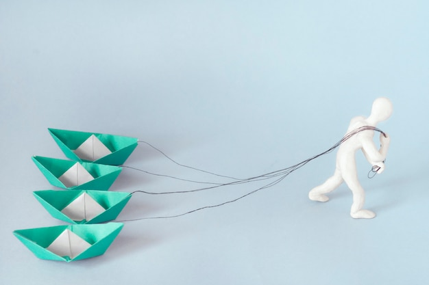 Man pulls on the ropes four paper green boats. concept of business, success, hard work.