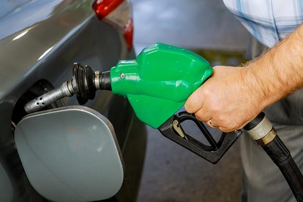 クローズアップで燃料で満たされているガソリンスタンドでガソリン車をポンプ男