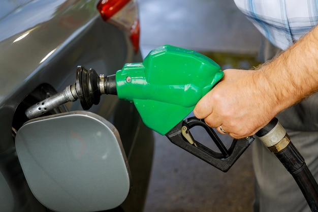 Man pumping gasoline car at gas station being filled with fuel on closeup