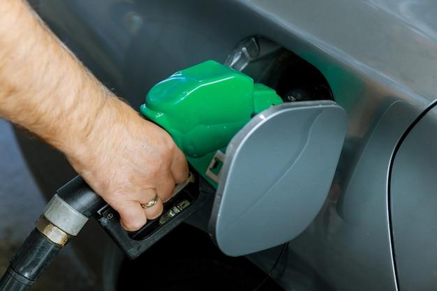 男はガソリンスタンドで車の輸送でガソリン燃料をポンプ