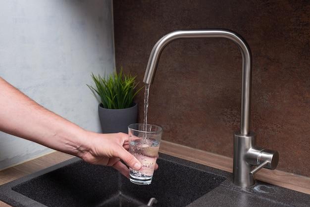현대 부엌에서 유리에 남자 순수한 물