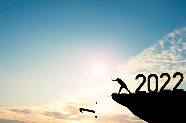 Man push number zero down the cliff where has the number 2022 with blue sky and sunrise. it is symbol of starting and welcome happy new year 2022