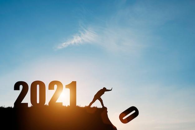 남자는 푸른 하늘과 일출로 숫자 2021이있는 절벽 아래로 숫자 0을 밀어 넣습니다.
