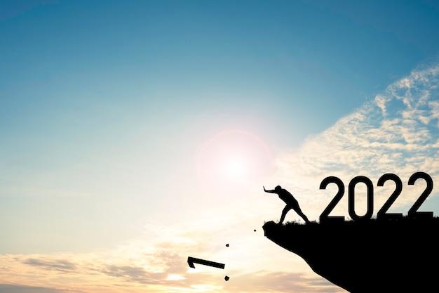 남자는 푸른 하늘과 일출로 숫자 2022가있는 절벽 아래로 숫자 0을 밀어 넣습니다. 시작의 상징이며 새해 복 많이 받으세요 2022
