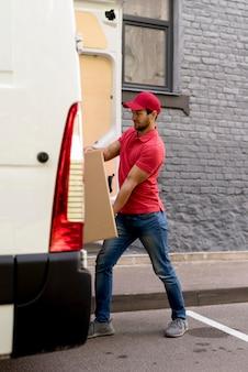 Человек толкает пакеты в машине