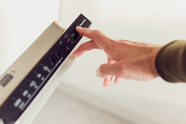 Man pushing start button on the control panel of the dishwasher.