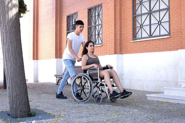 Man pushing wheelchair with woman