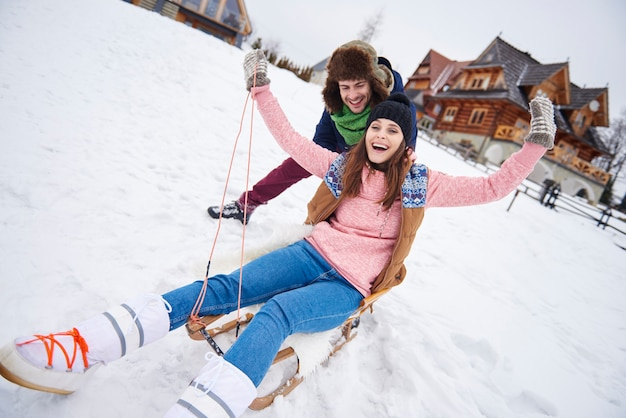 Man pushing woman down the hill on the sled