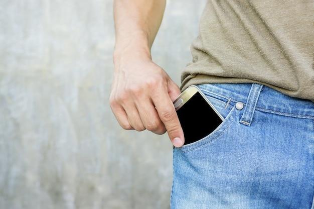 男はスマートフォンをジーンズのポケットに入れました。