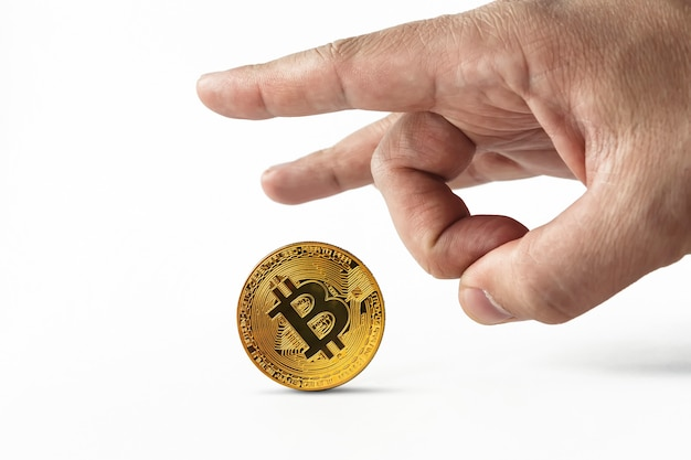Man put bitcoin on edge and pulls it away kicking with index finger. depreciation of virtual money bitcoin. concept of depreciation of cryptocurrency. cryptomoney downfall. throwing useless bitcoin.