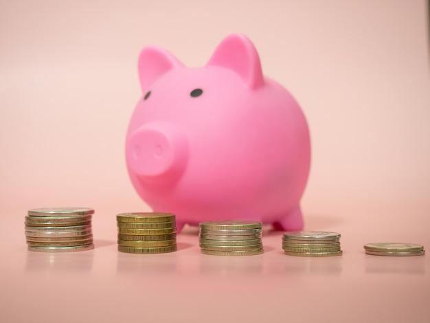 남자는 분홍색 배경, 클로즈업에 돼지 저금통에 동전을 넣습니다. 텍스트를 위한 장소