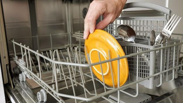 남자는 식기 세척기에 더러운 접시와 칼 붙이를 넣습니다. 상위 뷰, 클로즈업 손입니다.