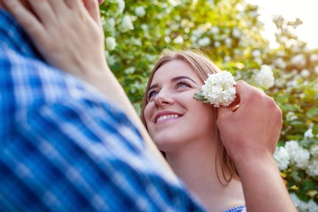 Мужчина кладет цветок в волосы подруги