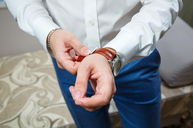 男は彼の手に時計を置きます
