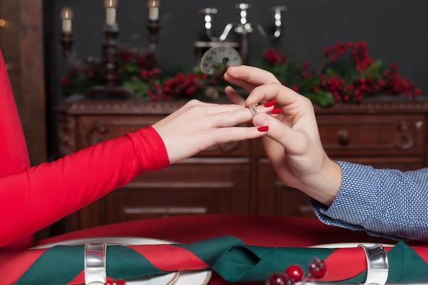 Мужчина кладет обручальное кольцо на руку женщины