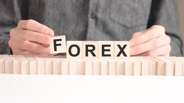 남자는 forex라는 단어에서 문자 f로 나무 큐브를 넣습니다.