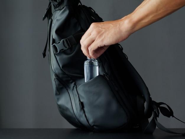 A man puts alcohol gel in a black modern backpack. sanitizer