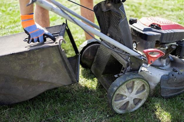남자는 빈 잔디 깎는 기계를 제자리에 놓습니다.