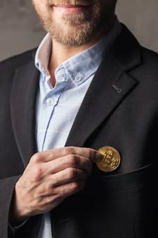 男はジャケットのポケットにビットコインを入れます。
