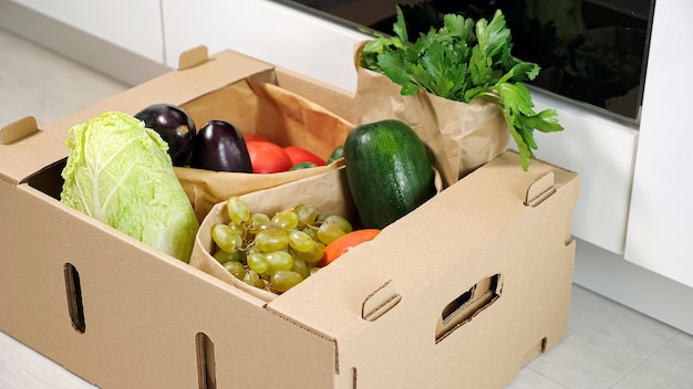 男は、キッチンのクローズアップで床にさまざまな野菜と茶色の段ボール容器を置きます