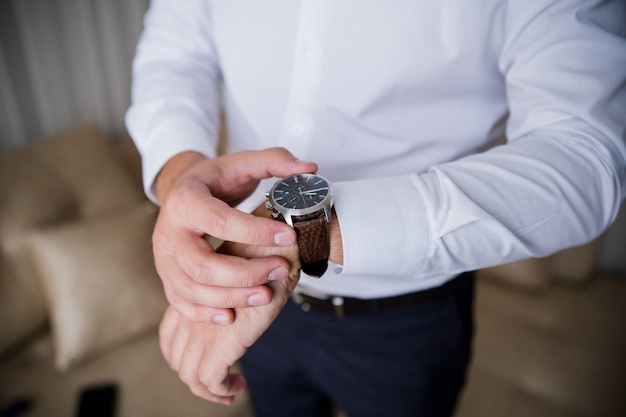 A man puts a classic watch on his hand