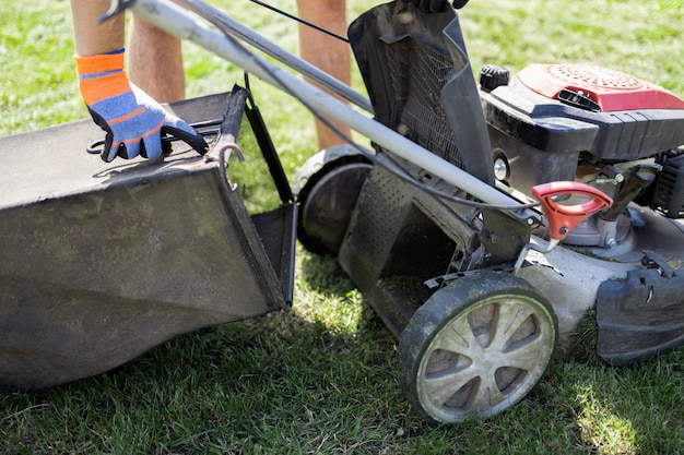 Man puts an empty lawn mower catcher in place