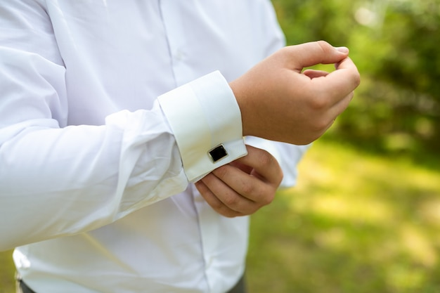 A man puts on an expensive shirt with cufflinks in the morning.