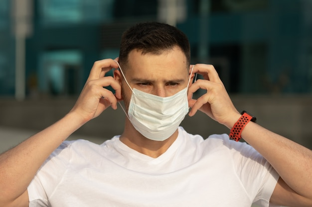 Man puts on a face mask. light blue face mask during a pandemic virus crown for protection against viruses and bacteria. covid-19.