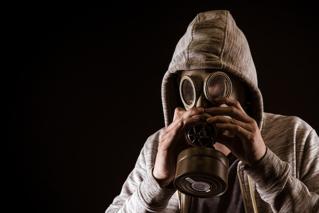 Man puts on gas mask to protect against gas. portrait on black background, dramatic coloring