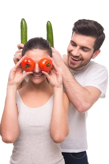 A man puts the horns of a girl with cucumbers.