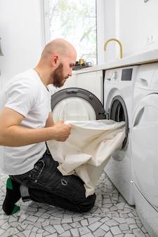 Мужчина кладет белье в стиральную машину