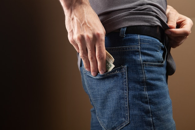 Man puts money in his back pocket on brown background