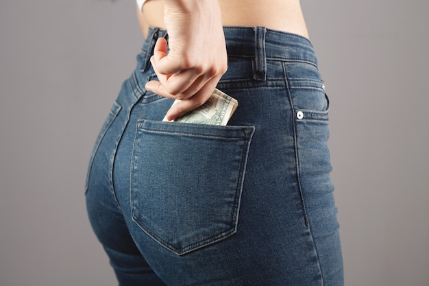 Man puts money in his back pocket on gray background
