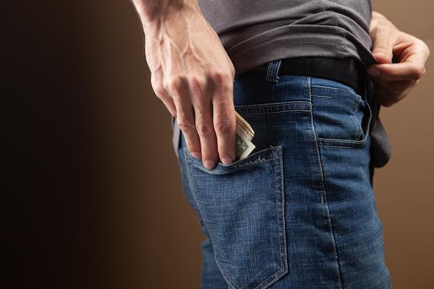 茶色の背景に男が後ろポケットにお金を入れる