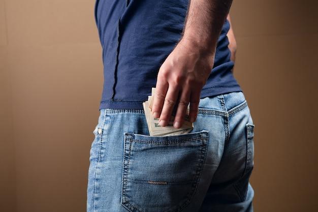 남자는 갈색에 그의 뒷 주머니에 돈을 넣습니다.