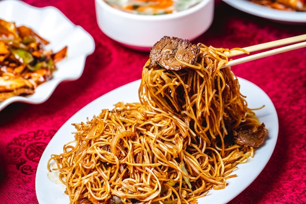 Man puts noodles by sticks onion meat soya sauce side view