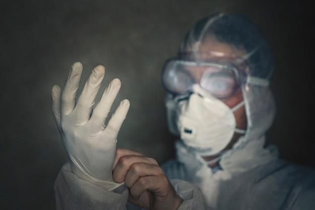 男は抗ウイルススーツを着ます。手に手袋をクローズアップします。暗い部屋で。夜に働きます。疫学保護スーツを着た医師。