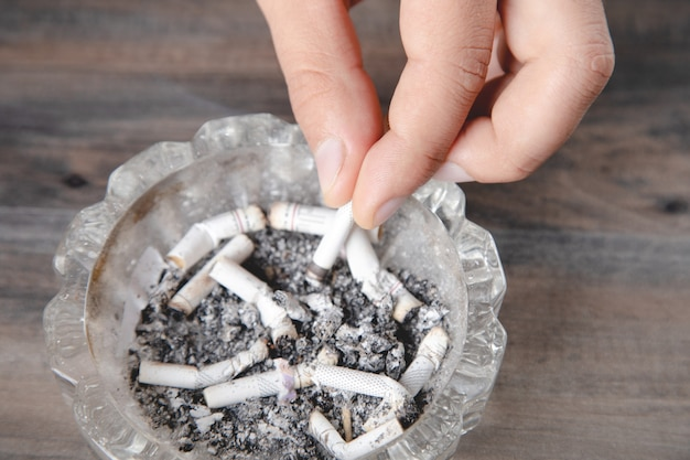 A man puts out a cigarette in an ashtray
