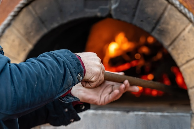 Мужчина ставит пиццу в профессиональную кирпичную печь с красным светом из-за огня внутри духовки