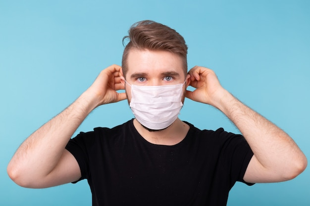 Man puts on a protective medical mask in blue studio to be safe from viruses and infections
