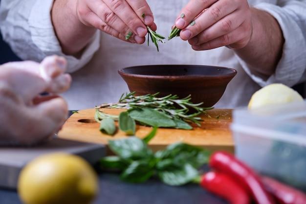 男はローズマリーを皿に入れます。オーブンでスパイスとレモンを使って鶏肉を調理するプロセス。