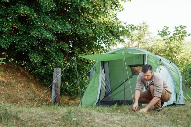 A man puts a tent in the forest.