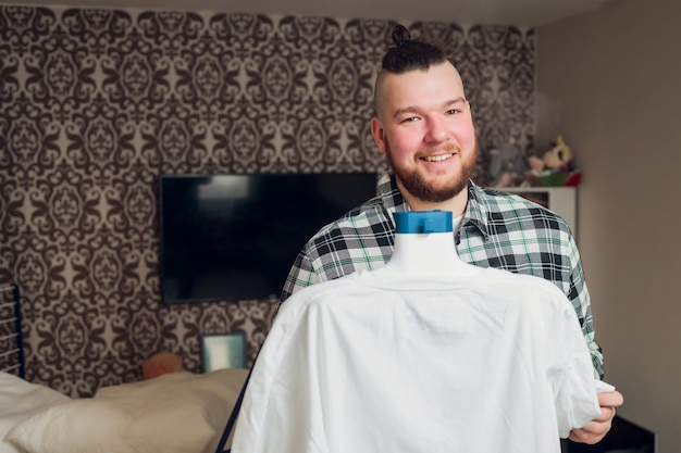 A man puts things in order holds the garment steamer in his hand and smoothes the jacket after washing