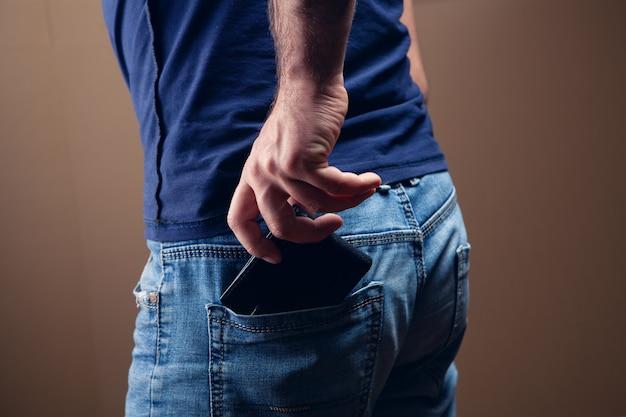 남자는 갈색 바탕에 뒷 주머니에 지갑을 넣습니다.