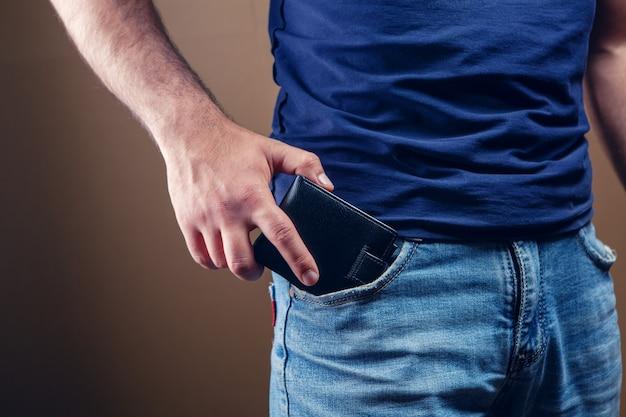 남자는 갈색 바탕에 앞 주머니에 지갑을 넣습니다.