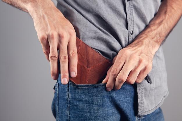 Мужчина кладет кошелек в передний карман на сером фоне